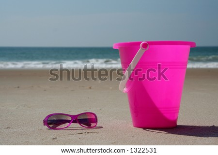 Sun glasses and pail sitting on the beach with waves in the distance - stock photo