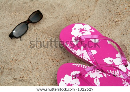 Sun glasses and pink flip-flops in the sand at the beach - stock photo