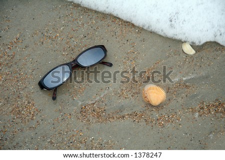 Sun glasses in the sand at the beach with an approaching wave.  There's some motion blur in the wave. - stock photo