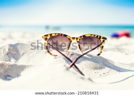 Sun glasses lie on a beach near the sea - stock photo