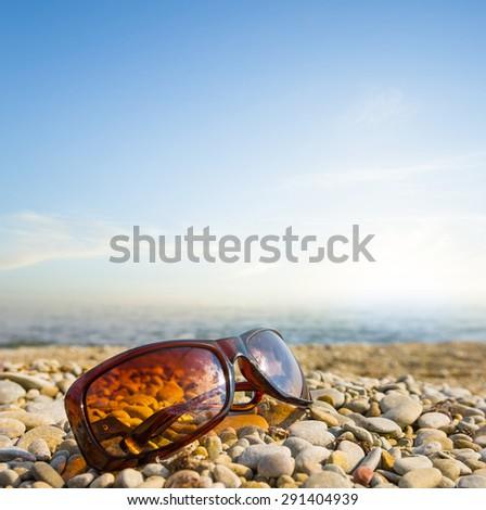 sun glasses on a sea coast - stock photo