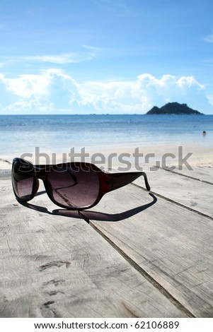 Sun glasses on wood over the blue sky - stock photo