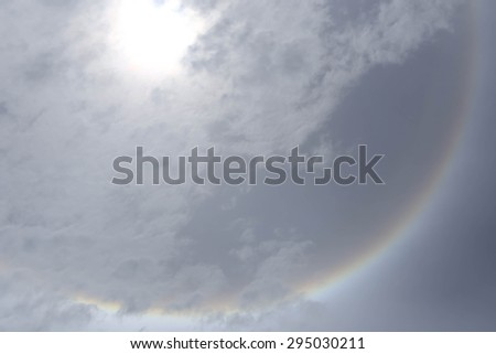 sun halo phenomenon with circular rainbow  in sky with cloud - stock photo