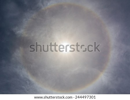 Sun halo with circular rainbow, due to ice crystals in atmosphere.  - stock photo
