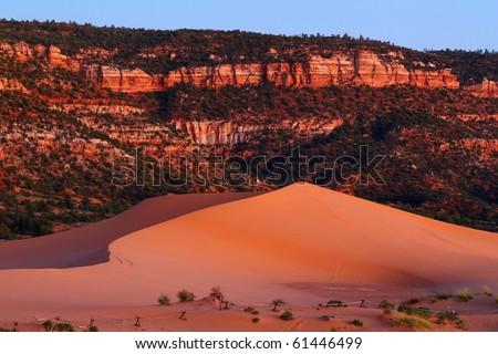 Sun has barely set and near-full moon illuminates dune and mountain cliffs of Coral Pink Sand Dunes State Park near Kanab, Utah. - stock photo