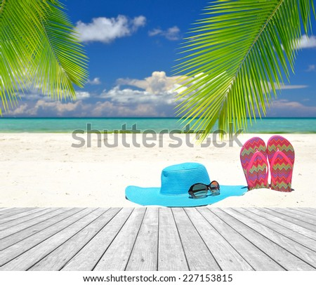 Sun hat with sunglasses and flip-flops on white sandy beach -- Summer holidays concept  - stock photo