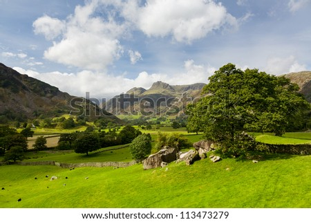 Sun illuminating Langdale Pikes in English Lake District - stock photo
