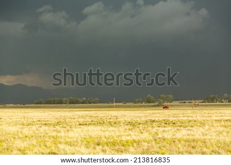 Sun illuminating prairie grassland with dark and forbidding thunderclouds and downpour with red van riding along lonely country road - stock photo