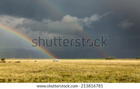 Sun illuminating prairie grassland with dark and forbidding thunderclouds and downpour with van riding along lonely country road and rainbow ending over the vehicle - stock photo