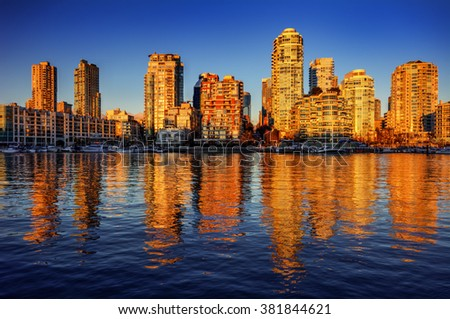 Sun illuminating the building, yachts moored, and reflections of building on the river - stock photo