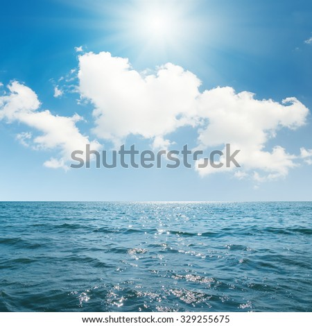 sun in blue sky with clouds over sea - stock photo