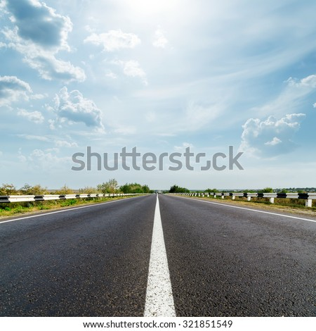 sun in dramatic sky over asphalt road - stock photo