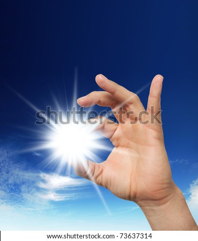 Sun in the hand on the blue sky. Freedom, harmony, spirituality concept - stock photo