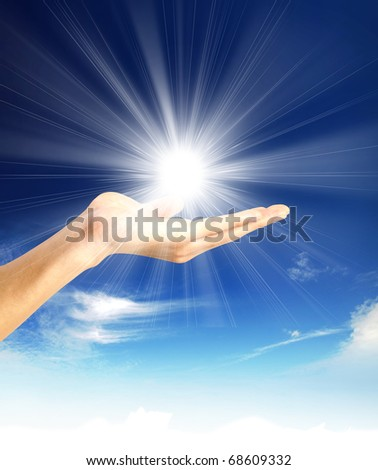 Sun in the hands on the blue sky. Freedom, harmony, spirituality concept