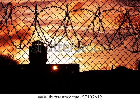Sun in the orange sky setting over prison yard