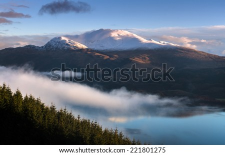Sun just touched the top of mountain Ben Lomond in Scotland. - stock photo