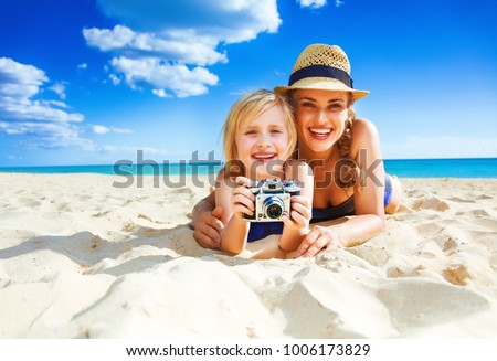 Sun kissed beauty. Portrait of smiling healthy mother and child in beachwear on the beach with retro photo camera