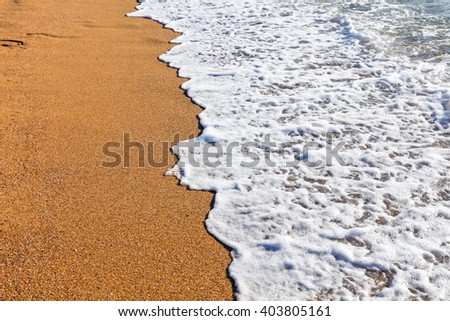 Sun light reflected on soft wave of the sea on the sandy beach - stock photo