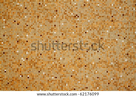 Sun lit wall with tan brown white mosaic tiles - stock photo