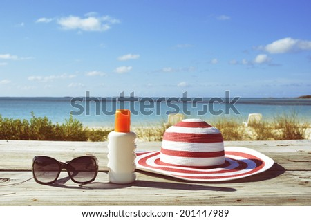 Sun lotion and sunglasses - stock photo