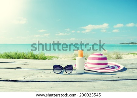 Sun lotion, sunglasses and hat - stock photo