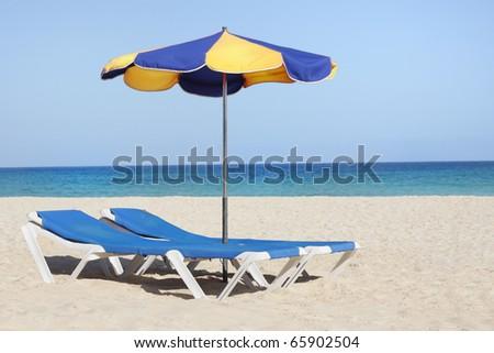 sun lounger chair on a beautiful beach - stock photo