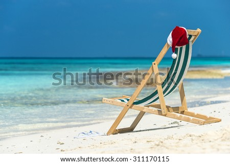 Sun lounger with Santa hat at beautiful tropical beach with white sand and turquoise water, perfect Christmas vacation - stock photo