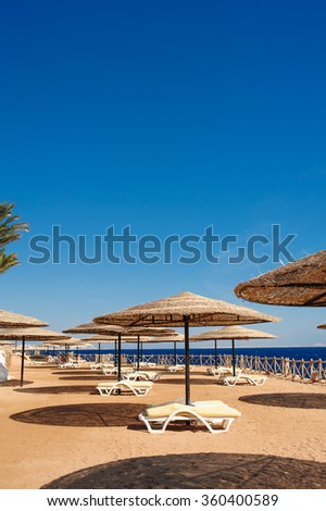 sun loungers and a beach umbrella on a beach perfect vacation concept. - stock photo