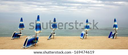 Sun loungers and a beach umbrella on a deserted beach island Sardinia Italy - stock photo