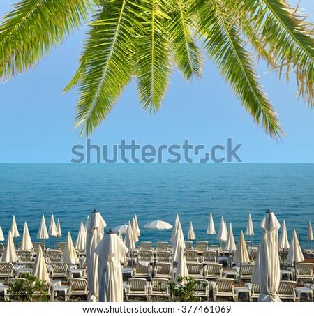 Sun loungers and a beach umbrellas on a beach. Vacation concept. - stock photo