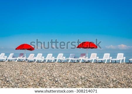 Sun loungers and red umbrellas on the beach in Batumi, Georgia - stock photo