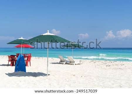 Sun loungers, chairs, table and umbrella on a tropical beach in Cancun, Mexico. - stock photo