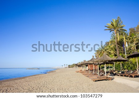 Sun loungers on a sandy beach by the Mediterranean Sea at the popular resort of Marbella in southern Spain, Costa del Sol, Andalusia region, Malaga province. - stock photo