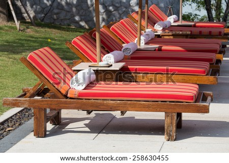 Sun loungers with towels near the swimming pool - stock photo