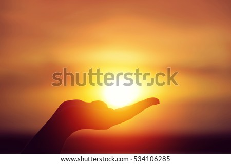 Sun on female hand. Silhouette of hand holding sun