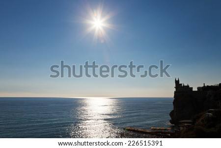 sun over Black Sea and Aurora cliff with Swallow's Nest castle on Southern Coast of Crimea - stock photo