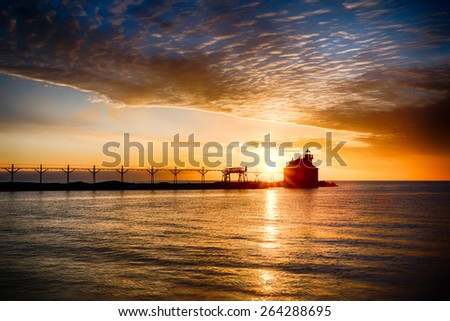 Sun over the water and lighthouse - stock photo