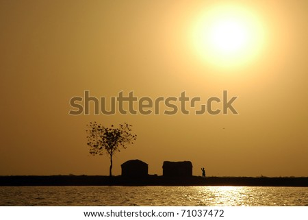 Sun over traditional West African huts along the Niger river shore - stock photo