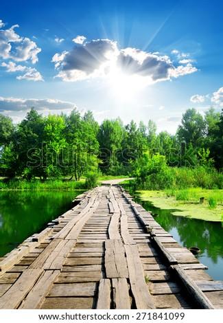 Sun over wooden bridge through calm river - stock photo