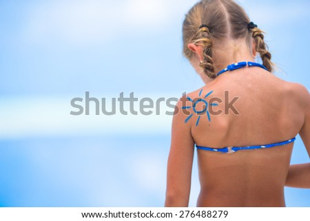 Sun painted by sun cream on kid shoulder - stock photo