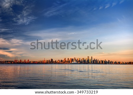 Sun painting the city skyline gold, blue water and sky - stock photo