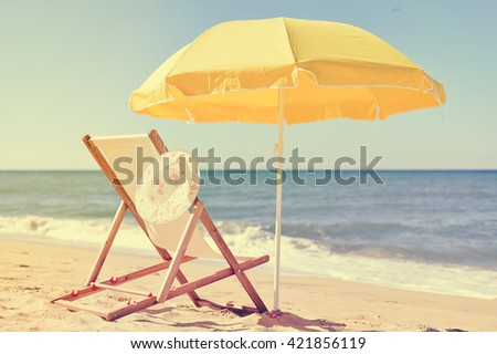 Sun parasol, chair longue and female hat on vacation beach sun shine outdoors - stock photo