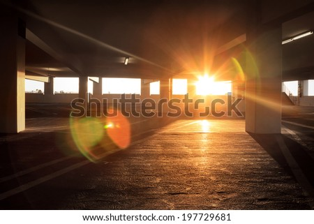 Sun peeking into large dark empty grunge parking structure industrial interior. - stock photo