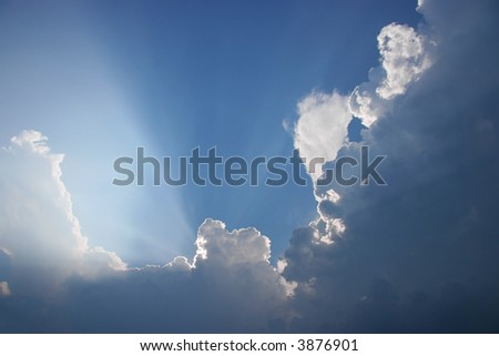 Sun projecting rays behind dramatic clouds in the blue sky before a thunderstorm