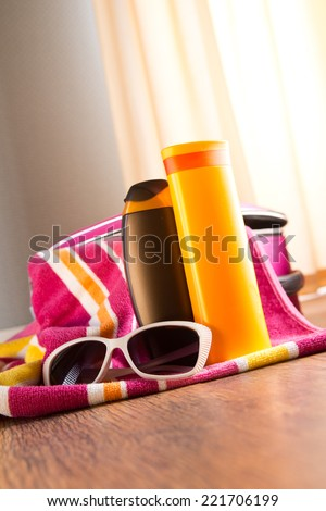 Sun protection cosmetics and sunglasses on striped towel next to a bag. - stock photo