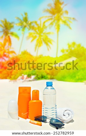 Sun protection cream and sunglasses on palm beach background. Tropical landscape. Retro style toned picture with light leaks - stock photo