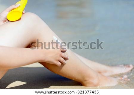 Sun protection cream on the leg close-up - stock photo