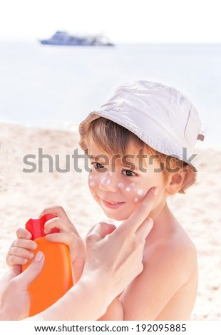 Sun protection. Hand of caucasian mother applying suncream  (suntan lotion) from a plastic container to her happy cute son before tanning during summer holiday on beach. Summer vacations concept.   - stock photo