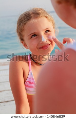 Sun protection. Mother anoints her daughter face protective cream on the beach - stock photo