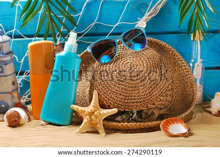 sun protection still life with suntan lotion bottles,straw hat and sunglasses on the beach  - stock photo